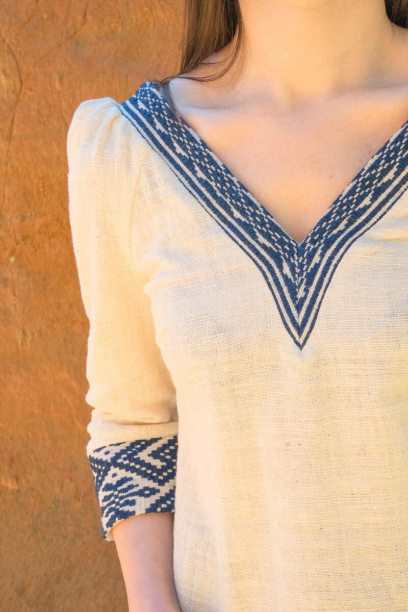 Femme portant blouse coton bio blanche et tissages traditionnels bleus