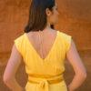 Femme de dos portant combinaison pantalon jaune ceinture soie