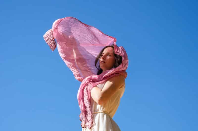 Femme en robe blanche éthique et foulard en soie rose